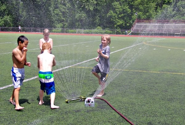 Boys playing in sprinkler at Sum It Up Lacrosse camps