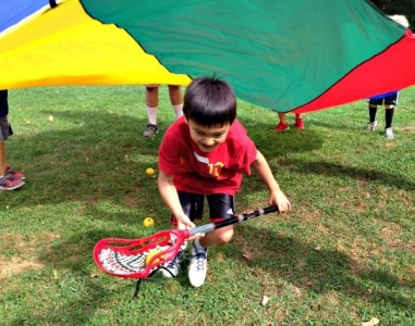 Boy playing parachute drill at Sum It Up Lacrosse