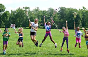 Happy Sum It Up Lacrosse players jumping with lacrosse sticks in hand
